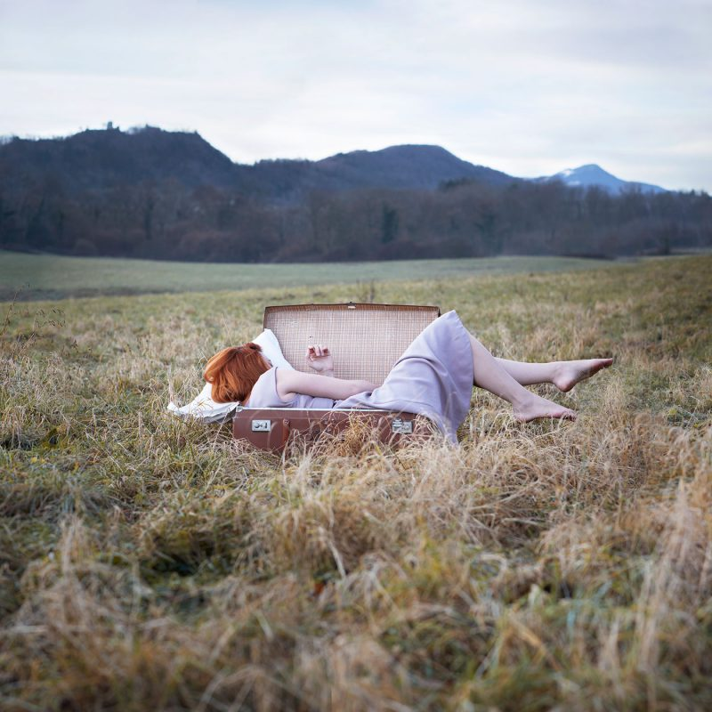 Delphine Millet Wake up - Staged photography delicate sensitive surrealist suitcase field alone dream travel nature - Art conceptual photographer in Berlin